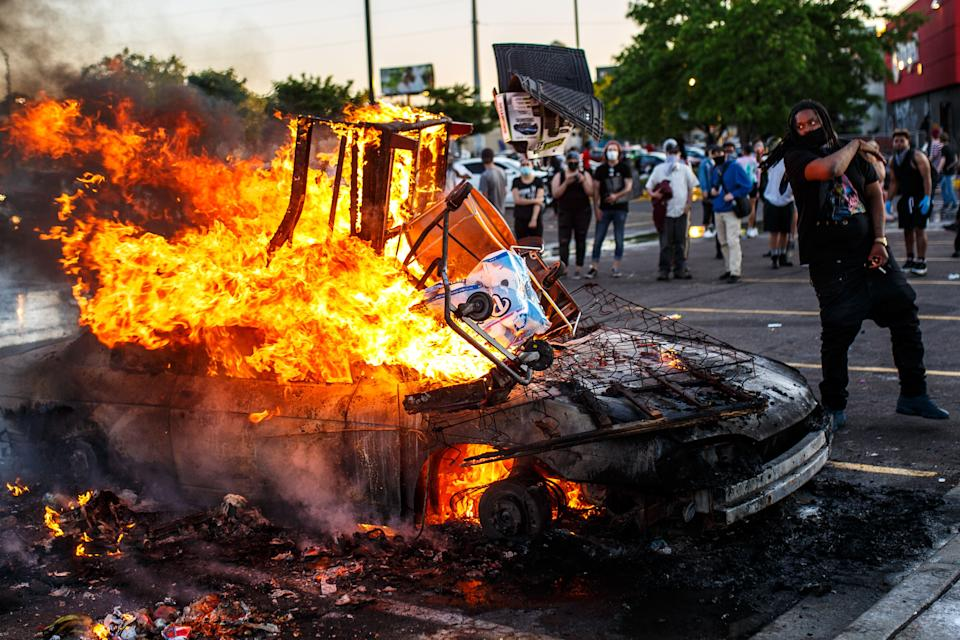 Protesters throw objects into a fire outside a Target store near the Third Police Precinct on May 28, 2020 in Minneapolis, Minnesota, during a demonstration over the death of George Floyd. (Photo by Kerem Yucel / AFP) (Photo by KEREM YUCEL/AFP via Getty Images)