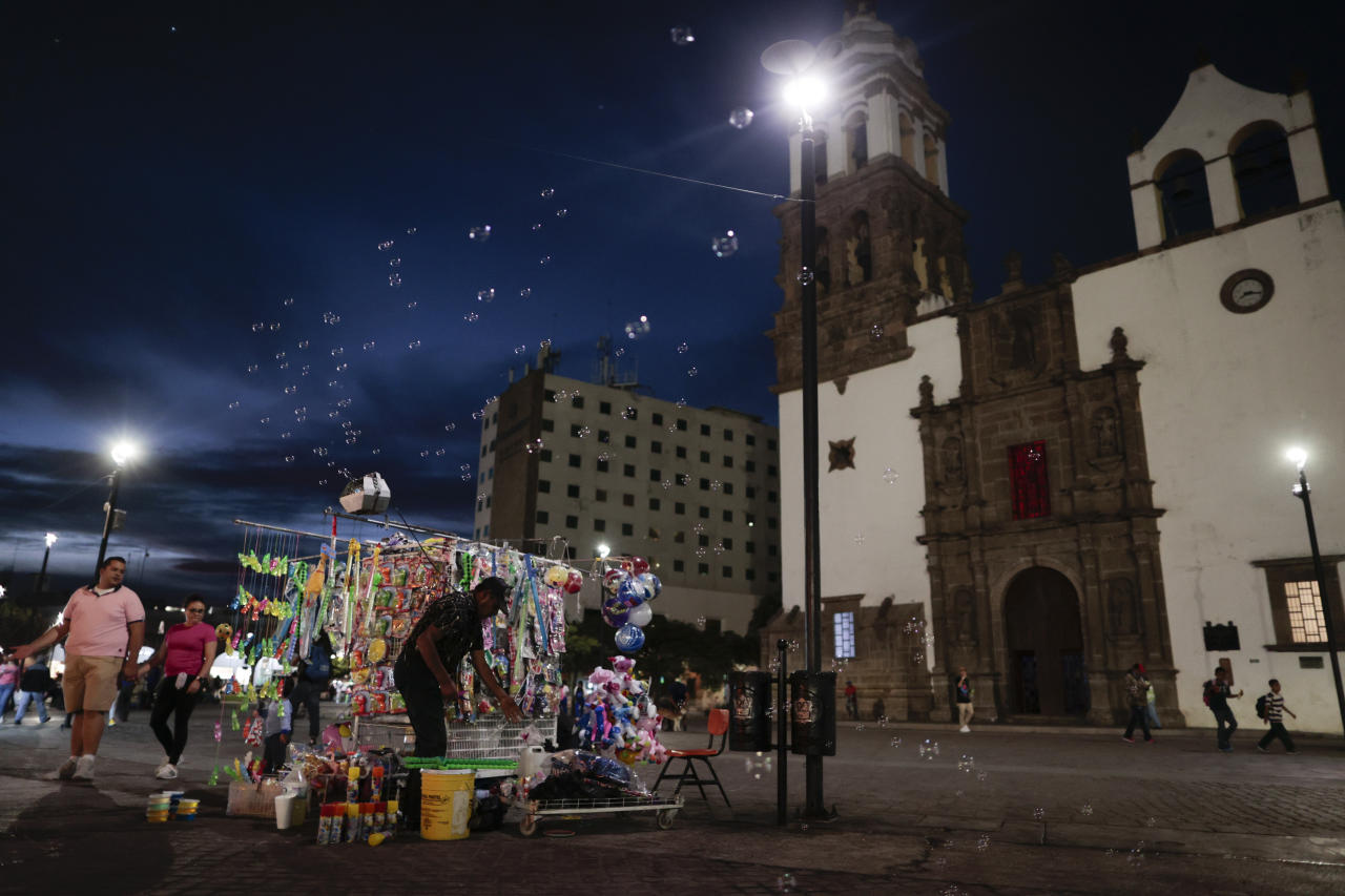 In this Feb. 12, 2020 photo, people and vendors mingle on a central plaza as night falls, in Irapuato, Guanajuato state, Mexico. The state is attractive to drug cartels for the same reason it is to auto manufacturers: road and rail networks that lead straight to the U.S. border. (AP Photo/Rebecca Blackwell)