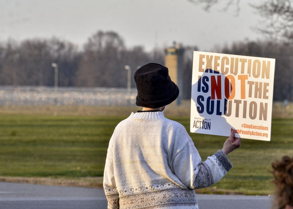 A protester holds an anti death penalty sign along Prairieton Road across from the Federal Execution Chamber Thursday, Dec. 10, 2020 in Terre Haute, Ind. The execution Brandon Bernard, convicted in the 1999 killing of two youth ministers in Texas is scheduled Thursday at the federal prison in Terre Haute, Indiana.. (Austen Leake/The Tribune-Star via AP)