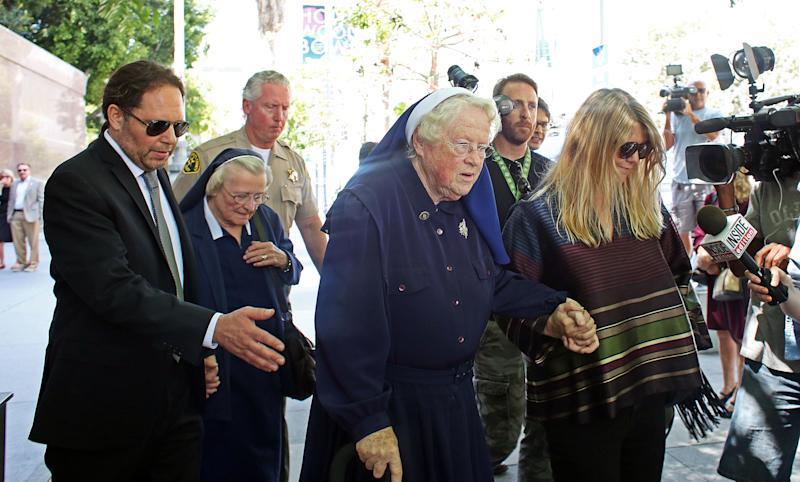 Sisters Catherine Rose Holzman, second left, and Rita Callanan, center, is escorted by businesswoman Dana Hollister, right, out of Los Angeles Superior Court on Thursday, July 30, 2015. The nuns are part of an order locked in a battle with Los Angeles' archbishop over the sale of their former convent, which pop singer Katy Perry wants to buy. A judge said Thursday that it appeared the nuns had improperly sold the property to Hollister, but warned the case will take months if not years to resolve. (AP Photo/Anthony McCartney)