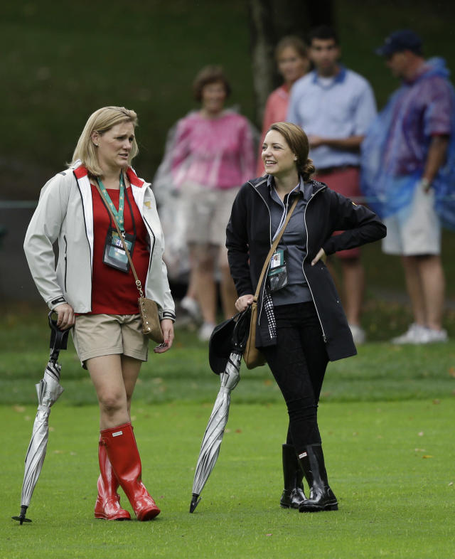 Kim Johnson, left, wife of United States team player Zach Johnson talks with Nieke Coetzee, girlfriend of International team player Branden Grace, of South Africa, during the single matches at the Presidents Cup golf tournament at Muirfield Village Golf Club Sunday, Oct. 6, 2013, in Dublin, Ohio. (AP Photo/Darron Cummings)