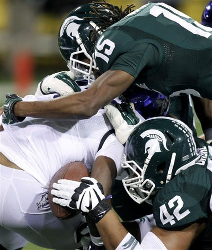 Michigan State defensive end Denzel Drone, bottom, pulls the ball away from TCU running back B.J. Catalon, center, as Michigan State cornerback Trae Waynes, top,hits Catalon during the first half of the Buffalo Wild Wings Bowl NCAA college football game, Saturday, Dec. 29, 2012, in Tempe, Ariz. Catalon's forward progress was stopped causing the referees to blow the play dead. (AP Photo/Paul Connors)