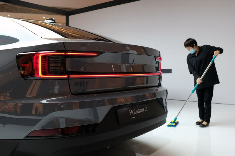 Worker cleans the floor near a Polestar 2 electric sedan at a shopping mall in Shanghai
