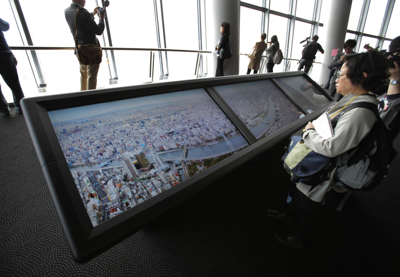 Journalists look at panoramic photos showing the view from the 450-meter (1,476 feet)-high observation deck during a press preview of the Tokyo Sky Tree in Tokyo Tuesday, April 17, 2012. The world's tallest freestanding broadcast structure that stands 634-meter (2,080 feet) will open to the public in May. (AP Photo/Itsuo Inouye)