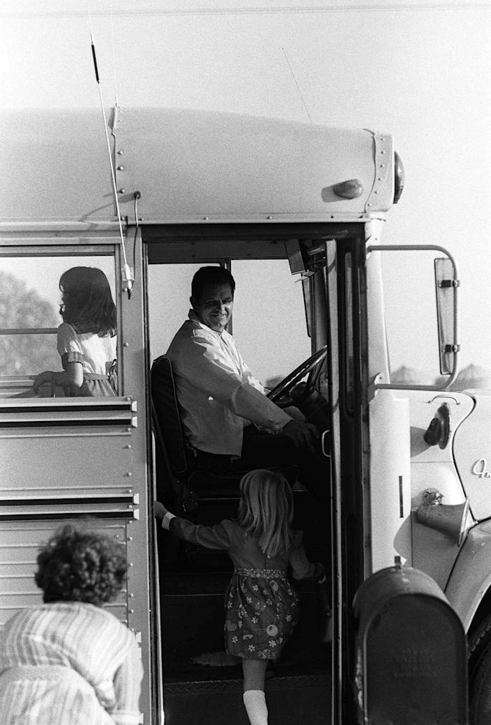 FILE - In this Sept. 13, 1976 file photo, bus driver Ed Ray, who was kidnapped with 26 school children from Chowchilla, waits for a passenger as school starts for the fall term. Ray, the school bus driver hailed as a hero for helping 26 students escape after three men kidnapped the group and buried the entire bus underground in 1976 died on Thursday, May 17, 2012. He was 91.(AP Photo)