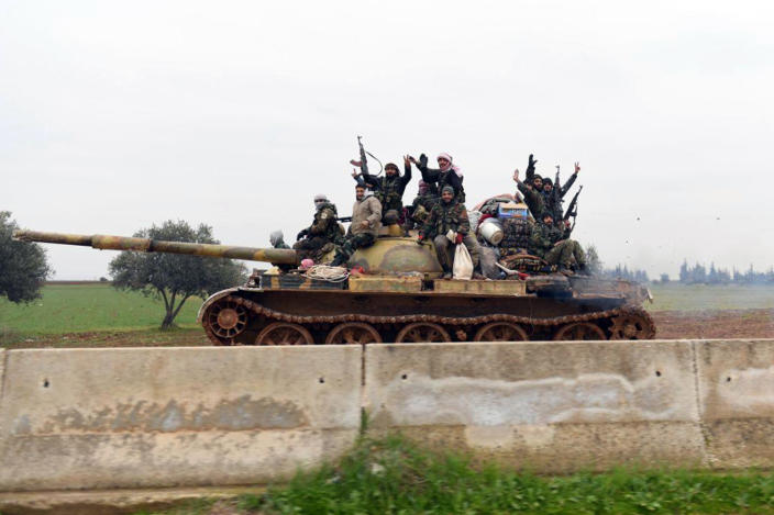 In this photo released Wednesday, Feb. 12, 2020, by the Syrian official news agency SANA, Syrian government soldiers on a tank hold up their rifles and flash victory signs, as they patrol the highway that links the capital Damascus with the northern city of Aleppo, Syria. The M5 highway, recaptured by President Bashar Assad's forces this week, is arguably the most coveted prize in Syria's civil war. The strategic highway is vital for Syria's economy as well as for moving troops. (SANA via AP)