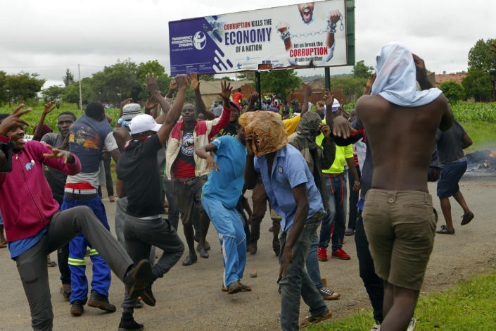 Protestors gather during a demonstration over the hike in fuel prices in Harare, Zimbabwe, Tuesday, Jan. 15, 2019. A Zimbabwean military helicopter on Tuesday fired tear gas at demonstrators blocking a road and burning tires in the capital on a second day of deadly protests after the government more than doubled the price of fuel in the economically shattered country. (AP Photo/Tsvangirayi Mukwazhi)