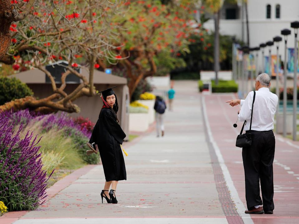 A graduate gets ready to pose for a picture at the empty campus of San Diego State University, after the California State University system announced the fall 2020 semester will be online, May 13, 2020.
