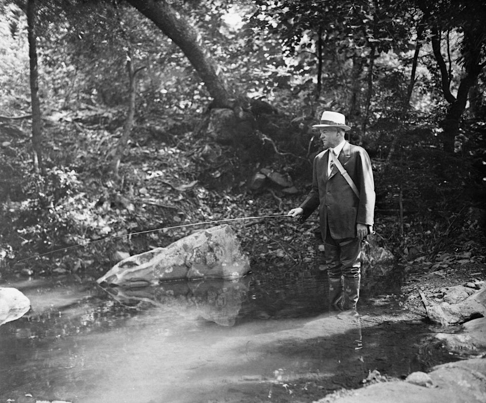 <p>Herbert Hoover wades into a creek and enjoys a quiet afternoon fishing, while vacationing at Camp Rapidan in Virginia in 1932. </p>