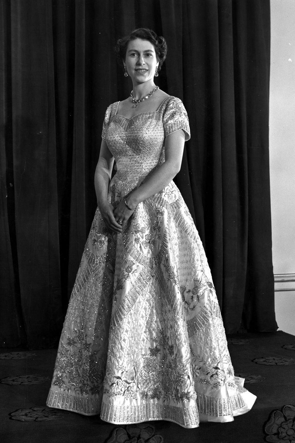 <p>In an embellished, cap-sleeved Norman Hartnell gown for her coronation ceremony. </p>
