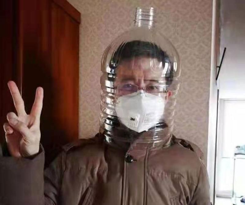 A man outside Wuhan Jinyintan Hospital gives a peace sign as he wears a medical facial mask with a plastic bottle over his head.