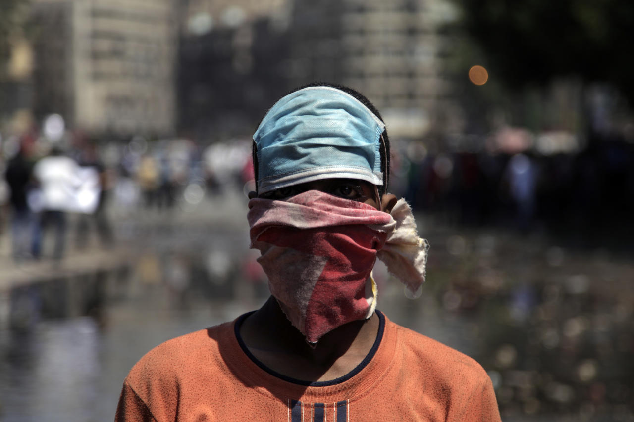 An Egyptian protester with covers his face during clashes with security forces, not shown, near the U.S. embassy in Cairo, Egypt, Friday, Sept. 14, 2012. The protests are part of widespread anger across the Muslim world about a film ridiculing Islam's Prophet Muhammad. (AP Photo/Khalil Hamra)
