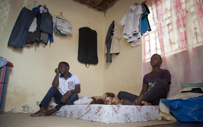 """In this photo taken Tuesday, March 25, 2014, two Ugandan homosexuals sit in the one-room safe-house where they now live, at an undisclosed location in Uganda. The enactment of Uganda's new anti-gay law has spread fear among homosexuals, forcing many to flee to so-called """"safe houses"""", often single rooms that are more likely to be locked up day and night because of safety concerns. (AP Photo)"""