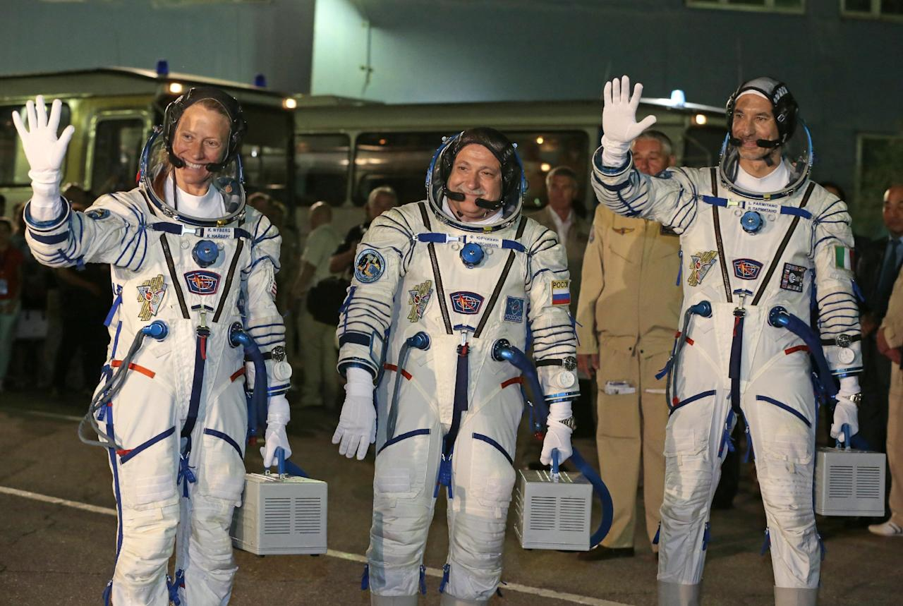 U.S. astronaut Karen Nyberg, left, Russian cosmonaut Fyodor Yurchikhin, center, and European Space Agency astronaut Luca Parmitano crew members of the mission to the International Space Station, ISS, pose prior the launch of their Soyuz-FG rocket at the Russian leased Baikonur cosmodrome, Kazakhstan, Tuesday, May 28, 2013. (AP Photo/Mikhail Metzel)