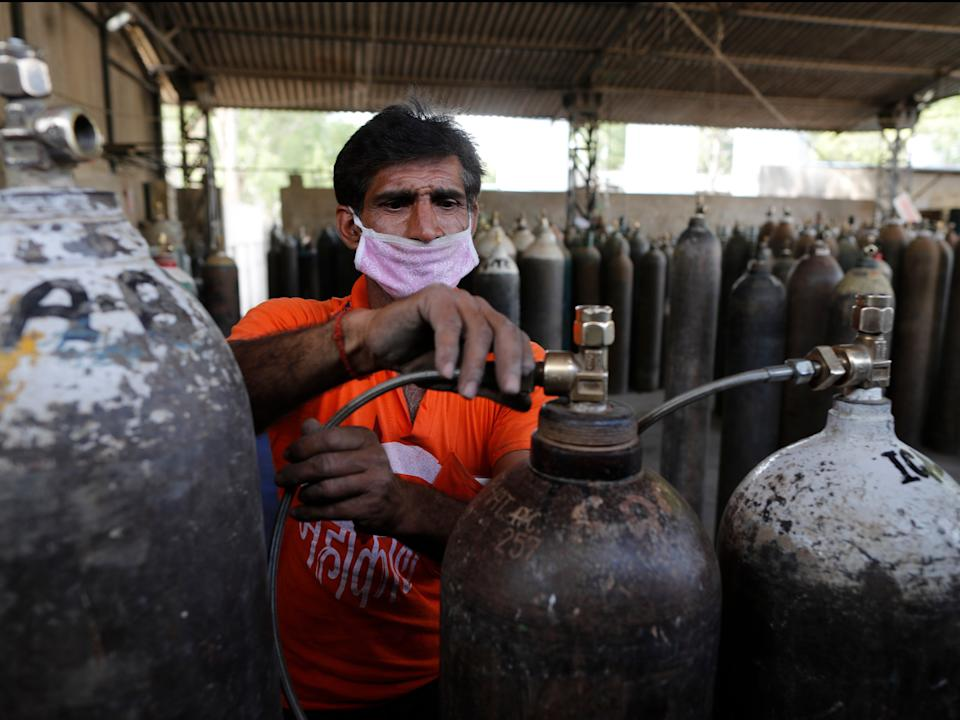 A worker refills medical oxygen cylinders at a charging station on the outskirts of Prayagraj (AP Photo/Rajesh Kumar Singh)