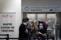 United Airlines passengers wait in line to register at the SFO COVID-19 rapid testing site at San Francisco International Airport in San Francisco, Thursday, Oct. 15, 2020. Coronavirus weary residents and struggling business owners in Hawaii will be watching closely as tourists begin to return to the islands on Thursday without having to self-quarantine upon arrival. (AP Photo/Jeff Chiu)