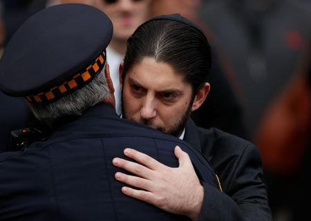 A family member embraces a police officer in front of Rodef Shalom Temple after funeral services for brothers Cecil and David Rosenthal, victims of the Tree of Life Synagogue shooting, in Pittsburgh, Pennsylvania, U.S., October 30, 2018. REUTERS/Cathal McNaughton
