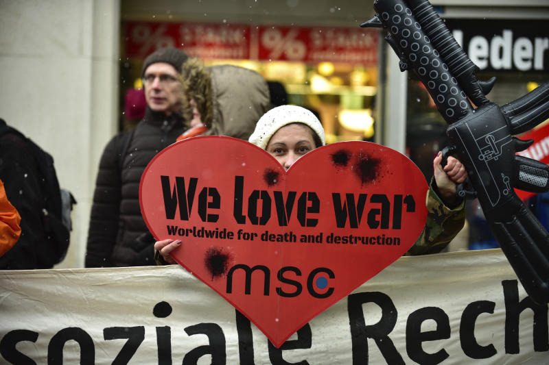 A demonstrator carries a poster reading: 'We Love War' as they protest against the Security Conference, MSC, in Munich, Germany, Saturday, Feb. 17, 2018. (Sebastian Gabriel/dpa via AP)