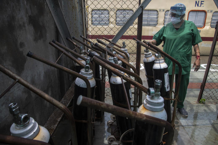 A health worker checks oxygen cylinders stored next to a train prepared as COVID-19 care centre in the wake of spike in the number of positive coronavirus cases, at a railway station in Gauhati, India, Thursday, May 6, 2021. Infections in India hit another grim daily record on Thursday as demand for medical oxygen jumped seven-fold and the government denied reports that it was slow in distributing life-saving supplies from abroad. (AP Photo/Anupam Nath)