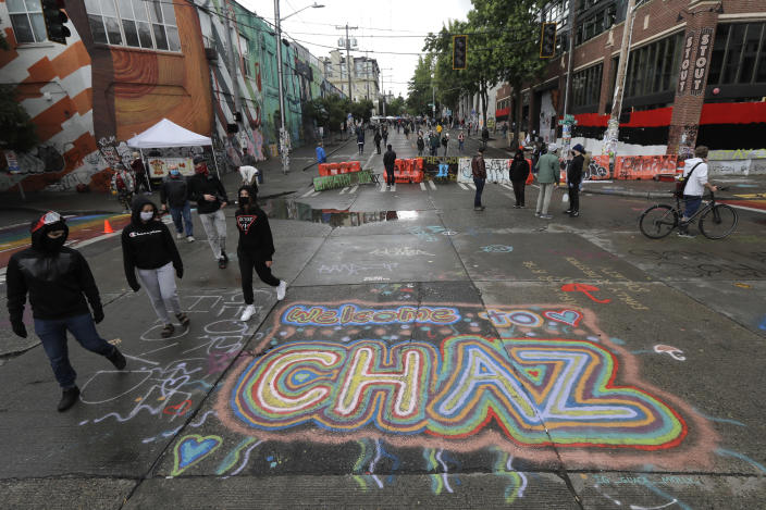 """FILE - In this Thursday, June 11, 2020 file photo, people walk past street art that reads """"Welcome to CHAZ"""" inside what is being called the """"Capitol Hill Autonomous Zone"""" in Seattle. On Friday, June 19, 2020, The Associated Press reported on a manipulated image circulating online incorrectly depicting residents of Seattle's occupied protest zone planting their new official flag, which has a pink unicorn and the acronym """"CHAZ"""" on it, in an overflowing trash can. The original version of the manipulated photo was posted in 2017, and does not show a unicorn or the acronym """"CHAZ"""" on the flag. There is no evidence that protesters in the Capitol Hill neighborhood have chosen any official flag. (AP Photo/Ted S. Warren)"""