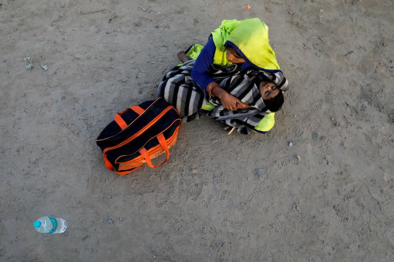 A migrant worker holds her baby as she sits along a highway waiting for a bus to return to their village, during a 21-day nationwide lockdown to limit the spreading of coronavirus disease (COVID-19), in Ghaziabad
