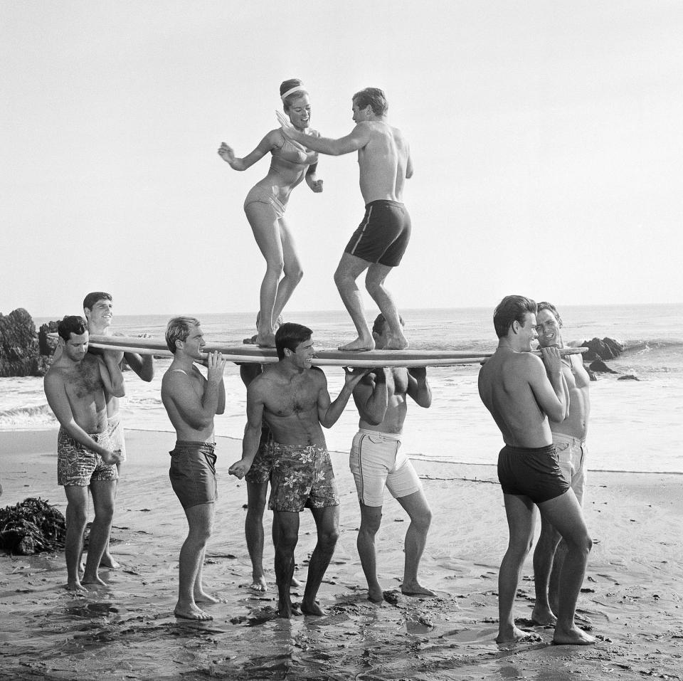 FILE - This 1965 file photo of youthful actors in a Hollywood movie amuse themselves between shooting scenes at California's Malibu Beach by staging an airborne twist exhibition on top of a surf board. For some Native Hawaiians, surfing's Olympic debut is both a celebration of a cultural touchstone invented by their ancestors, and an extension of the racial indignities seared into the history of the game and their homeland. The Summer Games in Tokyo, which kick off this month, serve as a proxy for that unresolved tension and resentment, according to the Native Hawaiians who lament that surfing and their identity have been culturally appropriated by white outsiders who now stand to benefit the most from the $10 billion industry. (AP Photo, File)