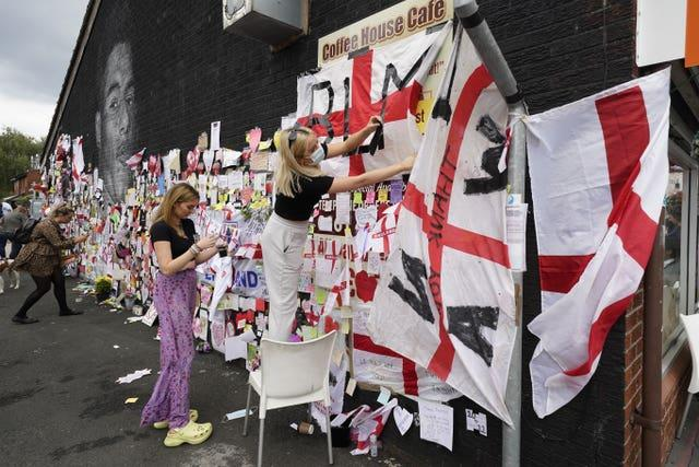 People put up flags and messages on the mural of Manchester United striker and England player Marcus Rashford (Danny Lawson/PA)
