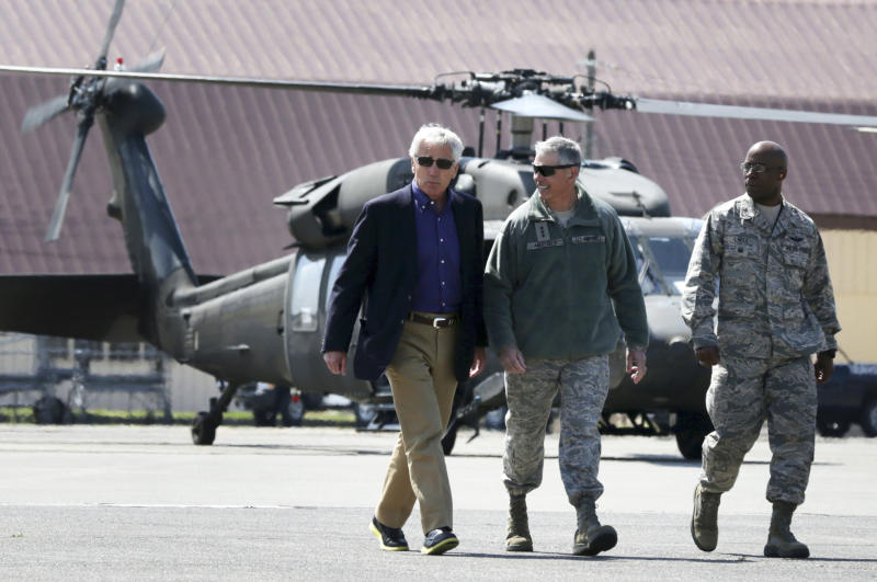 """Accompanied by Commander of U.S. Force Japan Lt. Gen. Salvatore """"Sam"""" Angelella, second from left, U.S. Secretary of Defense Chuck Hagel, left, walks on the tarmac of the Yokota Air Base, Japan, prior to his departure for Qingdao, China, Monday, April 7, 2014. Hagel is currently on his fourth trip to Asian nations since taking office. (AP Photo/Alex Wong, Pool)"""