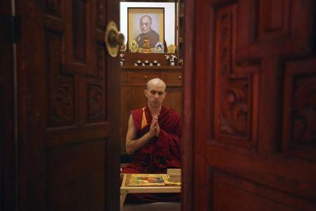 A Tibetan Buddhist monk meditates in front of a picture of Dalai Lama in Mexico City