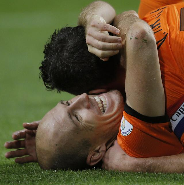 FILE - In this Oct. 11, 2013, file photo, Netherlands' Arjen Robben, bottom, is hugged by teammate Robin van Persie, who scored their fifth after a pass form Robben, during the Group D World Cup qualifying soccer match between Netherlands and Hungary in Amsterdam, Netherlands. Robin van Persie and Arjen Robben continue to spark the Oranje, but Van Persie must seize the opportunity after the Manchester United striker has scored only once at the last two major tournaments, the 2010 World Cup and Euro 2012. (AP Photo/Peter Dejong, File)