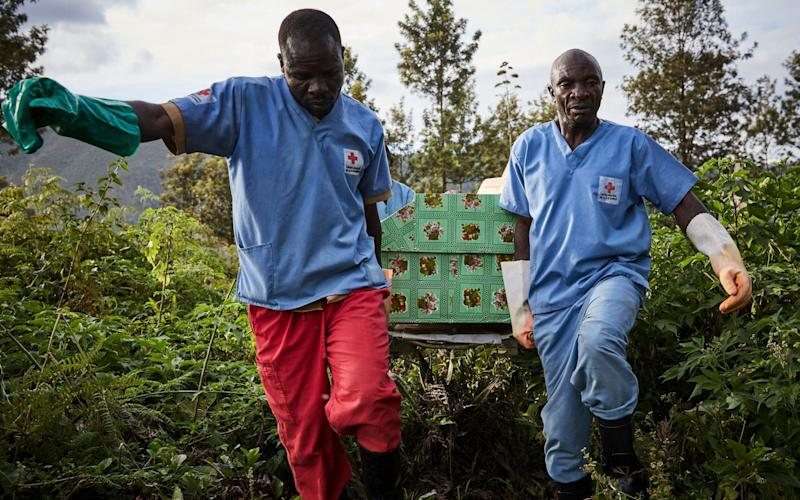 Health workers carry the coffin of an Ebola victim in Butembo, the town at the epicentre of the crisis - REX
