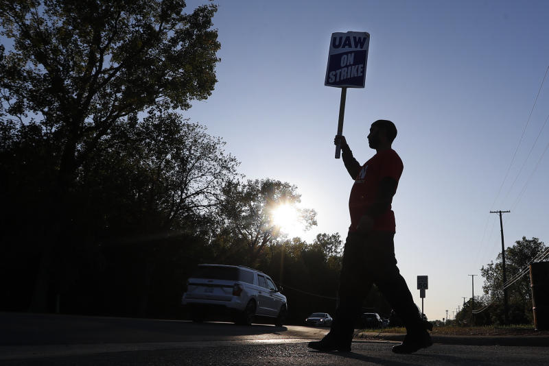 A member of the United Auto Workers walks the picket line at the General Motors Romulus Powertrain plant in Romulus, Mich., Wednesday, Oct. 9, 2019. Nearly four weeks into the United Auto Workers' strike against GM, employees are starting to feel the pinch of going without their regular paychecks. (AP Photo/Paul Sancya)