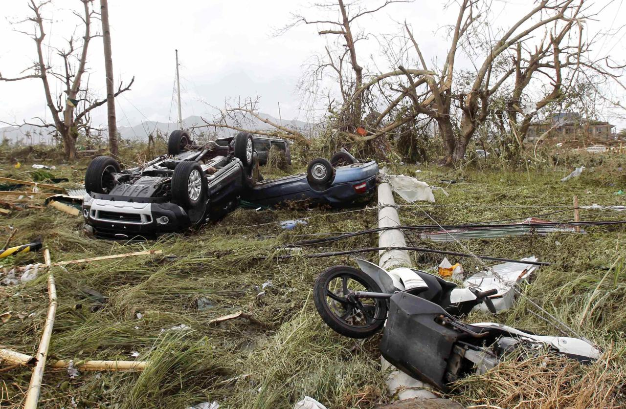 Overturned vehicles are seen at a rice field after super Typhoon Haiyan battered Tacloban city, central Philippines, November 9, 2013. Possibly the strongest typhoon ever to hit land devastated the central Philippine city of Tacloban, killing at least 100 people, turning houses into rubble and leveling the airport in a surge of flood water and high wind, officials said on Saturday. The toll of death and damage from Typhoon Haiyan on Friday is expected to rise sharply as rescue workers and soldiers reach areas cut off by the massive, fast-moving storm which weakened to a category 4 on Saturday. REUTERS/Romeo Ranoco (PHILIPPINES - Tags: DISASTER TPX IMAGES OF THE DAY ENVIRONMENT)