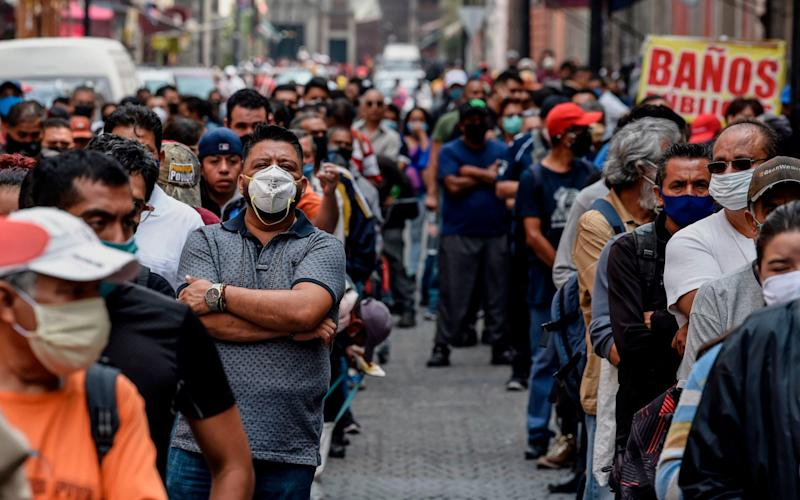 People queue in a street waiting to pass through a pedestrian control that limits the access in groups of 20 people to enter downtown Mexico City - AFP