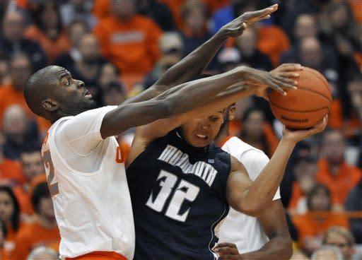 Syracuse's Baye Moussa Keita, left, pressures Monmouth's Ed Waite during the first half of an NCAA college basketball game in Syracuse, N.Y., Saturday, Dec. 8, 2012. (AP Photo/Kevin Rivoli)