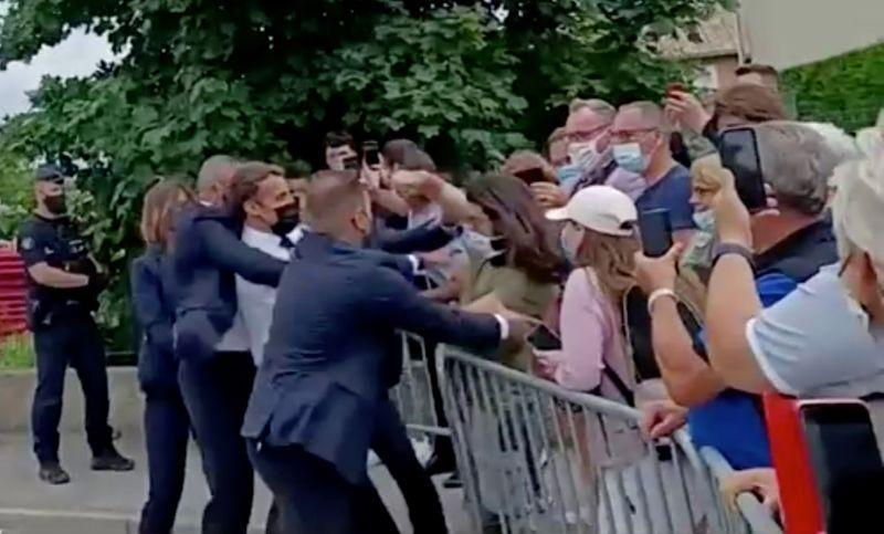 French President Emmanuel Macron is slapped in the face by a member of the public during a visit to Tain-l'Hermitage, France