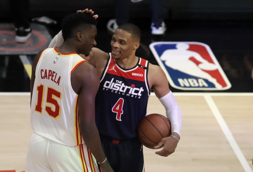 Russell Westbrook holds the game ball and pats Clint Capela on the head as Capela congratulates him.
