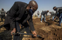 Mourners shovel earth into the grave of the late Duduzile Margaret Mbonane who died from COVID-19, during her funeral in Thokoza east of Johannesburg, South Africa, Thursday, July 23, 2020. Mbonane died just a month before her retirement, her husband said. Those on the front lines have been hit hard: The World Health Organization said Thursday more than 10,000 health workers have been infected in its African region, which is largely sub-Saharan Africa. (AP Photo/Themba Hadebe)