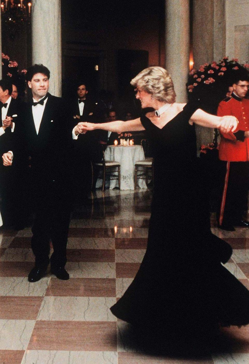 """<p>The velvet off-the-shoulder gown Princess Diana wore to a White House State Dinner in 1985 is one of the most iconic gowns worn by the royal. It was dubbed the """"<a href=""""https://www.townandcountrymag.com/society/tradition/a33445054/princess-diana-travolta-dress-kensington-palace-display-coronavirus/"""" rel=""""nofollow noopener"""" target=""""_blank"""" data-ylk=""""slk:Travolta Dress"""" class=""""link rapid-noclick-resp"""">Travolta Dress</a>"""" due to the heavily-circulated photo of Diana dancing with the movie star in it.</p>"""