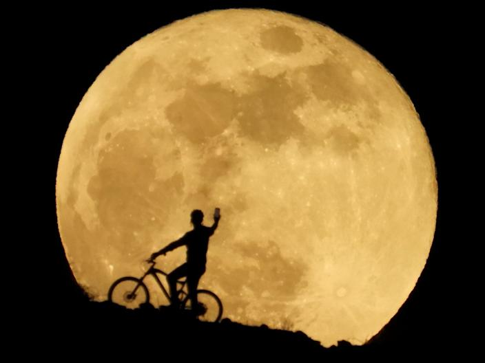 supermoon rises yellow over hill where cyclist holds up cellphone