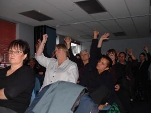 Many people raising their hands at a conference