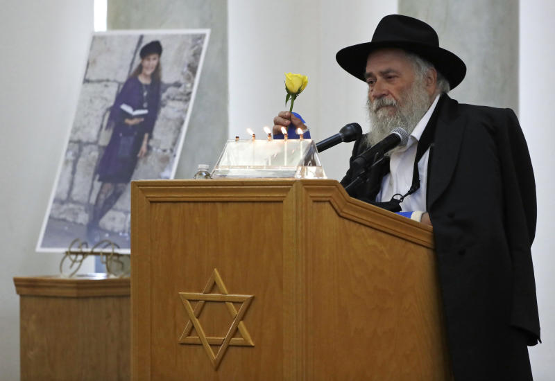 FILE - In this April 29, 2019, file photo, Yisroel Goldstein, Rabbi of Chabad of Poway, holds a yellow rose as he speaks at the funeral for Lori Kaye, who is pictured at left, in Poway, Calif. Kaye, who was was killed Saturday, April 27, when a gunman opened fire inside the Chabad of Poway synagogue, had given Goldstein the flower as part of a bouquet the day before the shooting, which also injured Goldstein. Details in newly released search warrants give the clearest indication that the New Zealand attacks on mosques inspired a San Diego man to open fire during a Passover service at the synagogue in April, killing Kaye and injuring three others. (AP Photo/Gregory Bull, File)