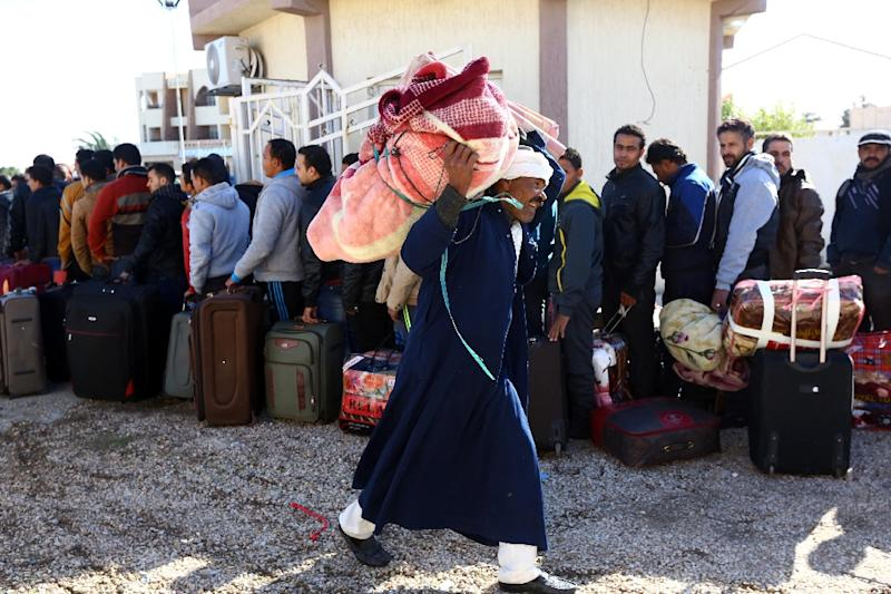Egyptians queue up with their belongings as they wait to enter Tunisia, via the Libyan side of the Ras Djir border crossing, on February 23, 2015 for a flight evacuating them back to Cairo