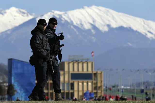 """Heavily-armed Russian military flash a """"thumbs up"""" while patrolling Olympic Park prior to opening ceremony at the 2014 Winter Olympics, Friday, Feb. 7, 2014, in Sochi, Russia. (AP Photo/Robert F. Bukaty)"""