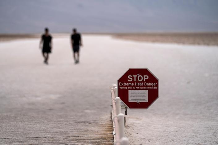 A sign warns hikers of extreme heat on the salt flats of Badwater Basin in Death Valley National Park, Calif., where the temperature reached 128 degrees on July 10, according to the National Weather Service.