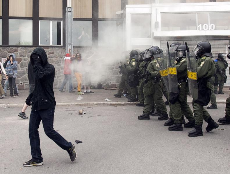 Quebec Provincial Police use tear gas to disperse students protesting against tuition hikes at the Lionel Groulx college Tuesday, May 15, 2012 in Ste. Therese, Quebec, Canada. About one-third of post-secondary students in Quebec are boycotting classes in a protest against tuition hikes that has lasted more than three months. What started as a battle over a $325-a-year fee hike appears to have morphed into a broader struggle over the role of the state, the legitimacy of protest tactics, and the boundaries of authority. (AP Photo/The Canadian Press, Ryan Remiorz)