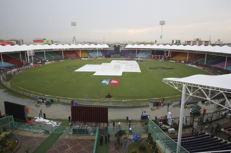 Officials cover the ground of the National Stadium after a rain in Karachi, Pakistan, Friday, Sept. 27, 219. Heavy rain has delayed the start of the first one-day international between Pakistan and Sri Lanka. An unusual spell of rain in the southern port city of Karachi during this time of the year left the cricket ground completely waterlogged on Friday. (AP Photo/Fareed Khan)