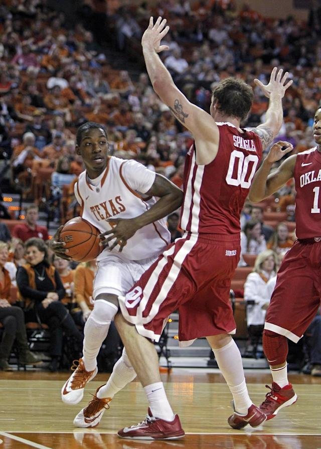Texas guard Damarcus Croaker (5) attempts to drive around Oklahoma forward Ryan Spangler (00) during the first half of an NCAA college basketball game, Saturday, Jan. 4, 2014, in Austin, Texas. (AP Photo/Michael Thomas)
