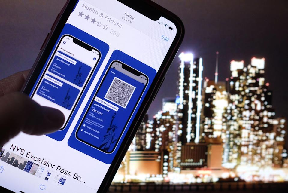 This illustration photo shows a person looking at the app for the New York State Excelsior Pass, which provides secure, digital proof of a COVID-19 vaccination, in front of a screen showing the New York skyline. In contrast to New York, states such as Texas and Florida are trying to ban businesses and other institutions from requiring proof of vaccination.