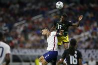 Jamaica defender Damion Lowe, top, leaps to head the ball over United States midfielder Sebastian Lletget, center left, as midfielder Daniel Johnson (16) looks on in the second half of a CONCACAF Gold Cup quarterfinals soccer match, Sunday, July 25, 2021, in Arlington, Texas. (AP Photo/Brandon Wade)